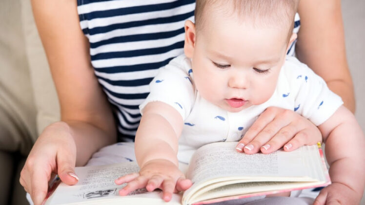 mom reading board book to one-year-old baby