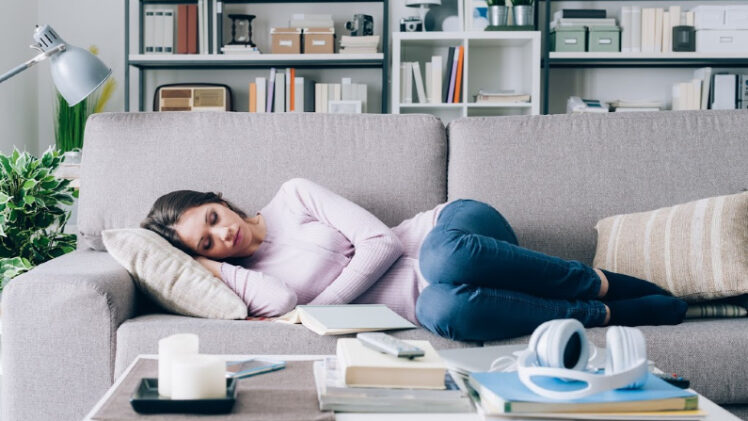 pregnant woman in her first trimester sleeping on the couch, not doing anything