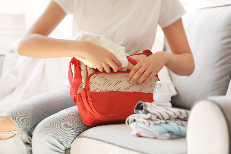 mom packing new mom survival kit in diaper bag