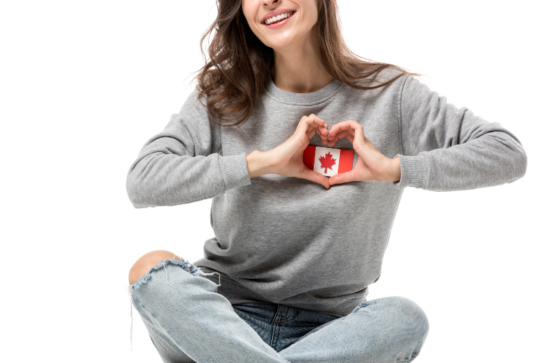 woman holding mini canadian flag over her heart