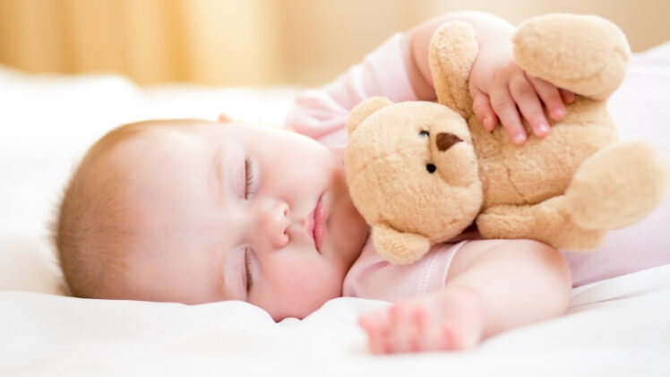 adorable sleeping baby girl holding teddy bear
