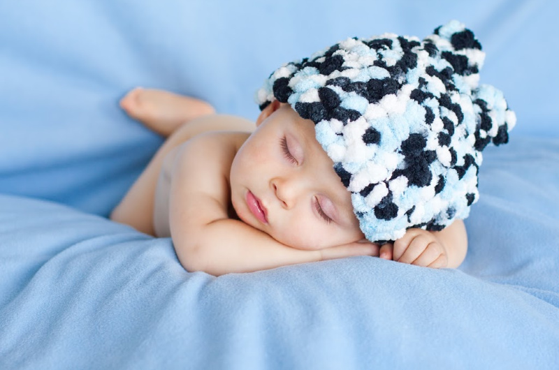 sleeping baby boy lying on blue blanket and fuzzy hat