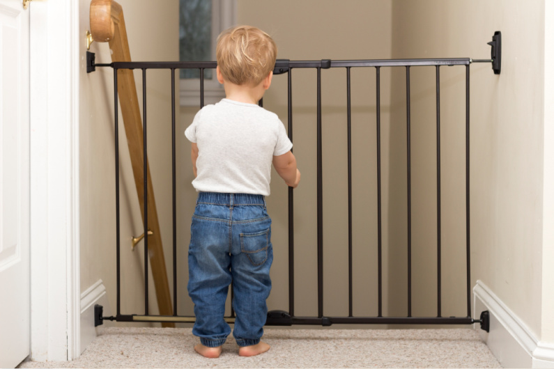 toddler holding onto baby gate looking down the stairs