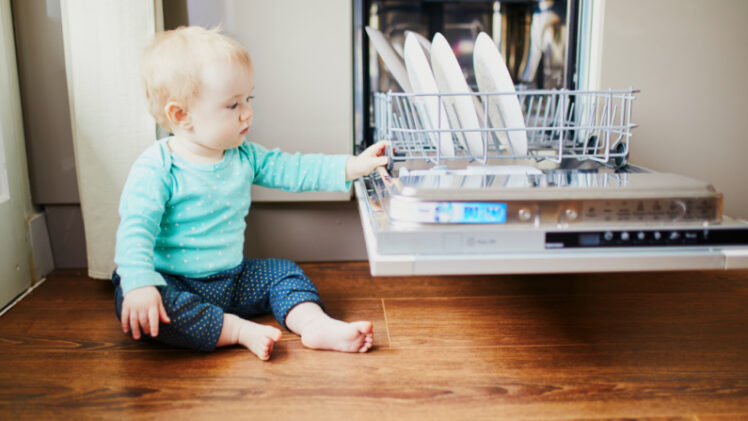 baby touching dishes in dishwasher