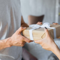pregnant woman giving Father's Day gift to expecting dad
