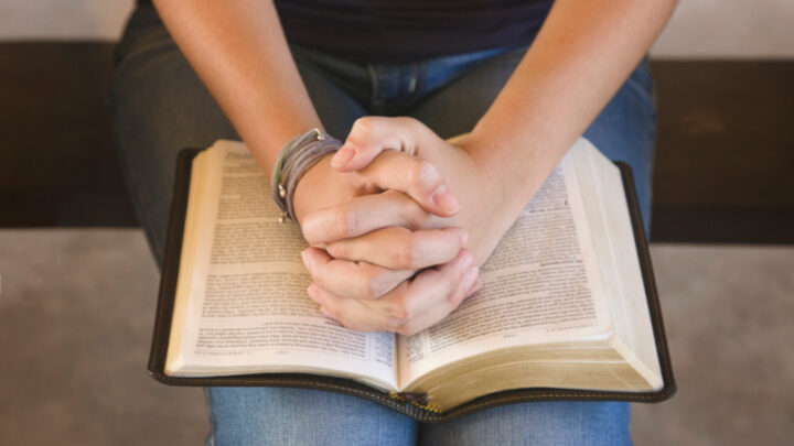 wife praying scriptures over her husband, folding hands on Bible