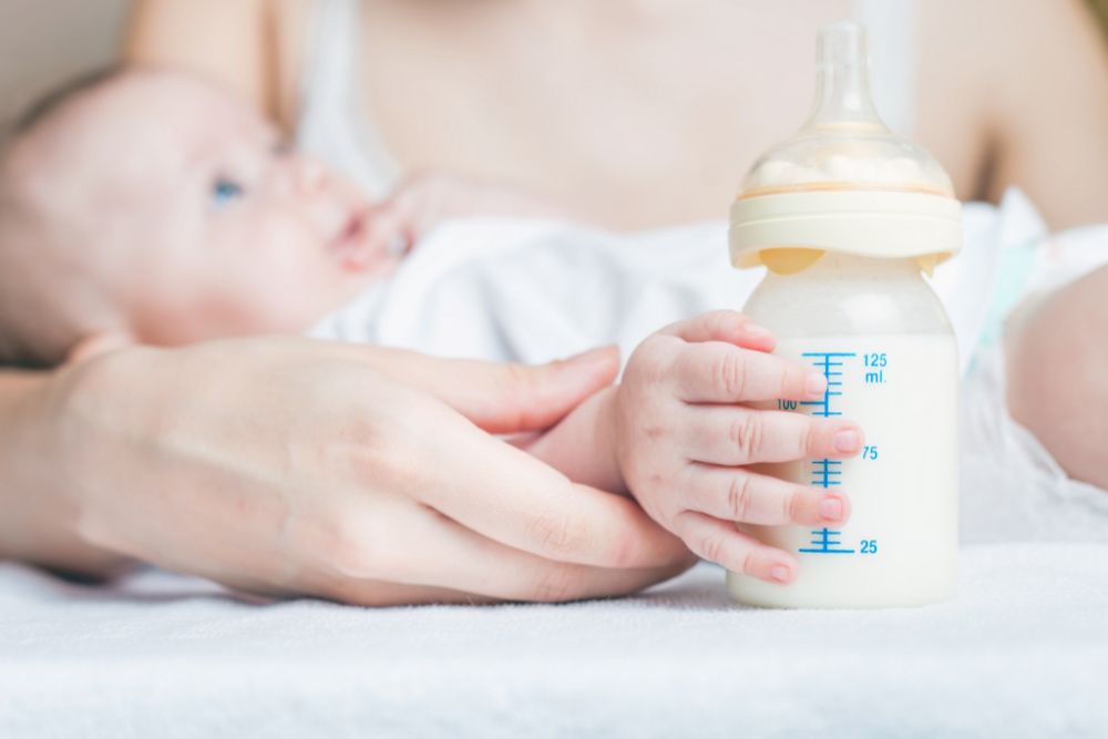 baby holding bottle with one hand while being held by mother