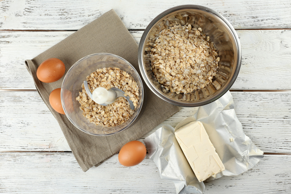 a few ingredients for oatmeal chocolate chip cookies with fenugreek on white wooden tabletop