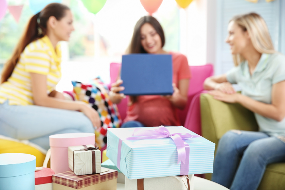 inexpensive baby shower gifts wrapped on a table while mom opens them, surrounded by friends