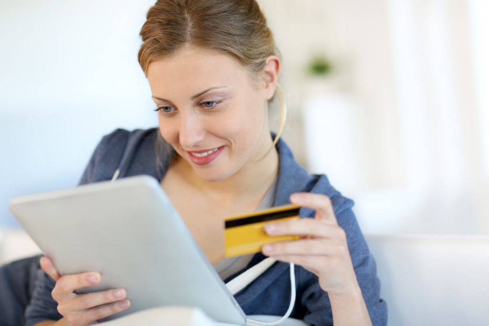 woman shopping online for inexpensive baby shower gifts, tablet and credit card in hand