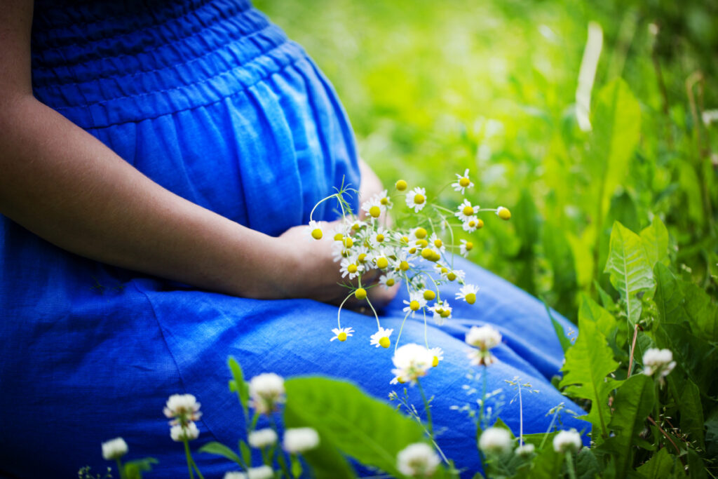 pregnant woman sitting in a field with flowers in her hand, considering plant names for boys