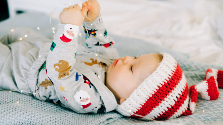 newborn baby lying on back dressed for christmas playing with christmas lights